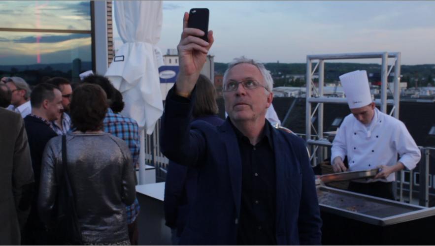 Ein Mann hält ein I-phone in die Luft