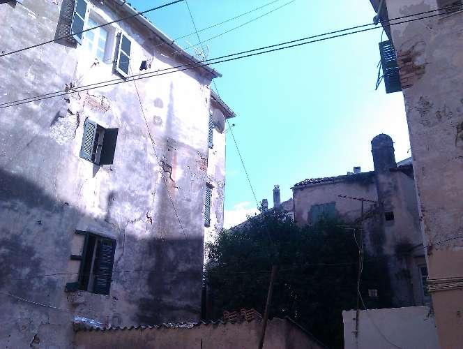 Blick auf ein altes Haus, teilweise ist die Fassade abgebröckelt und das Mauerwerk ist sichtbar.