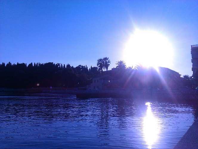 Blick auf das Meer. Die Sonne scheint in die Kamera, sodass sich ein großer Lichtreflex bildet